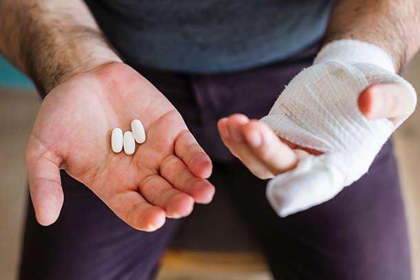 Man with one hand bandaged and the other holding pills