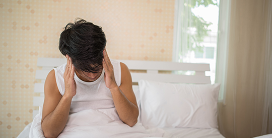 Man sitting in bed holding his head