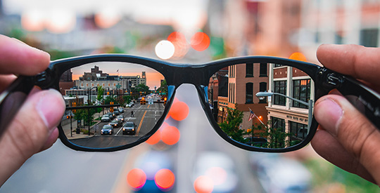 Person looking through glasses down a city street