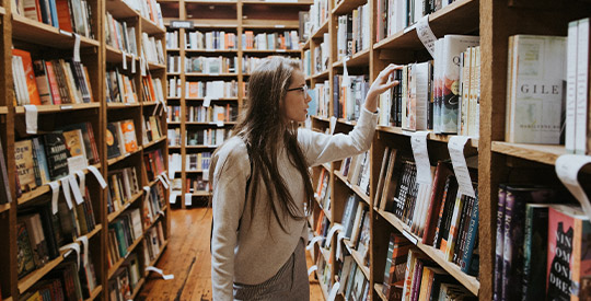 Woman picking book off of a shelf